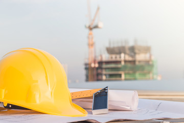 The yellow safety helmet and the blueprint at construction site