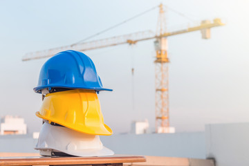 The safety helmet at construction site with crane background