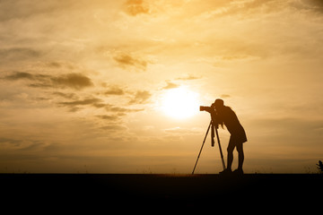 Silhouette of a photographer,she use a tripod,she wearing short dress and hat.The background image is a sunset in Thailand.