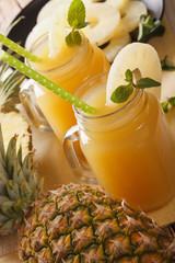 Fresh pineapple juice in a glass jar macro. vertical