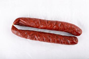 Smoked salami sausage on white.