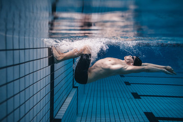 Pro male swimmer in action inside swimming pool