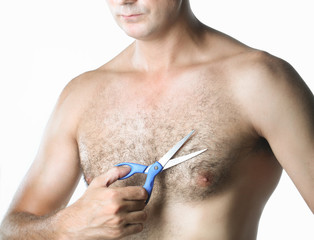 Man with scissors cuts hair on his hairy chest