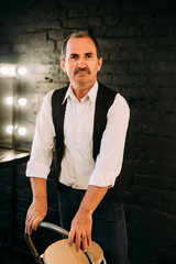 Handsome middle aged man is dressed in a white shirt and a black vest. Black background.