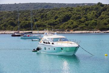 Luxury yacht in azure seas parked in a beautiful blue bay. Modern white Yacht in the sea around island on Croatia.