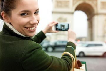 happy young woman visiting Paris. Triumphal arch.