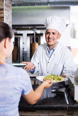 man cook serving fresh kebab dish to customer on counter in fast