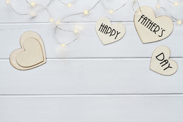 Overhead view of wooden hearts and fairy lights with message Happy Father's Day over a flat wood table top background with copy space available.