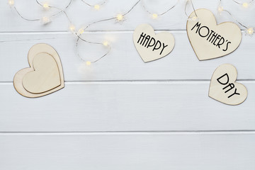 Overhead view of wooden hearts and fairy lights with message Happy Mother's Day over a flat wood table top background with copy space available.