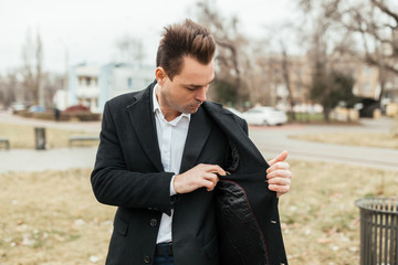 the man in a black coat and a suit goes on the street. He looks for something in an inside pocket of a coat. He has a business look.