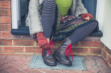 Woman tying her shoes on step outside