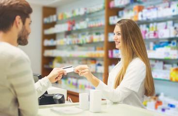 Experienced pharmacist counseling male customer in modern pharma