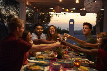 Friends make a toast at a dinner party on a patio, close up Wall mural