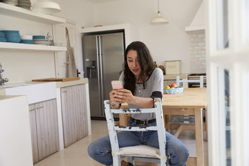 Teenage girl sitting in kitchen using smartphone, front view