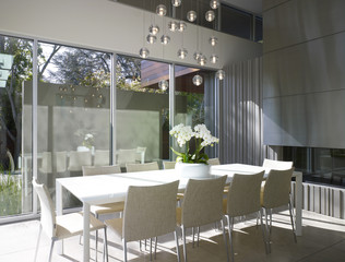 White dining table with light display at glass windows of Menlo Park Residence, California, USA.