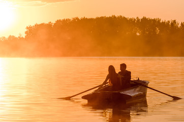 Love and romantic golden river sunset. Silhouette of couple on boat backlit by sunlight