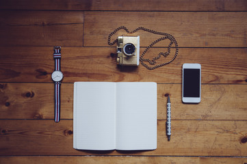 Paper notebook,watches,lomography film camera, pen and a touchscreen smartphone on the old wooden table background Wall mural