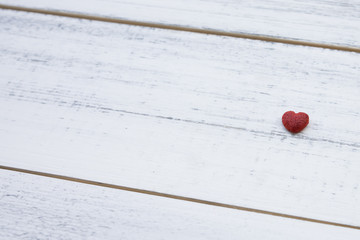 One red little heart on white wooden background with copy space