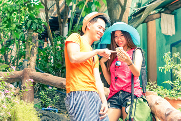 Happy filipino couple of tourists using mobile phone with man pointing at device screen