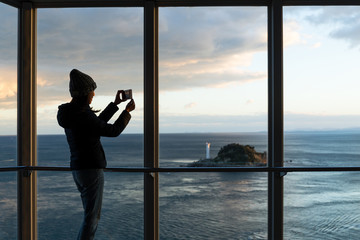 Woman taking photo with sunset inside tourist lookout