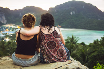 Two girls sitting and admiring the view from the mountain  Wall mural