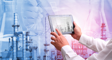 Petrochemical oil refinery with Flask in scientist hand with dropping liquid to test tube with  Industry 4.0 concept .Man hand holding  tablet  in smart factory