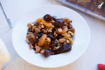Mix nuts, dry fruits and grapes in white plate