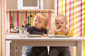 family baby brother and sister play eat meal in toy kitchen