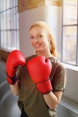 lachende frau mit boxhandschuhen im fitnessstudio