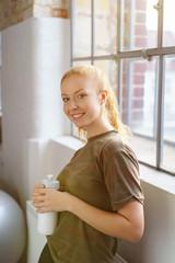 lächelnde frau macht eine pause im fitnessstudio