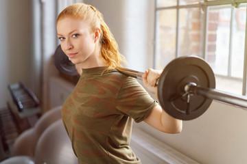 frau macht krafttraining im fitness studio
