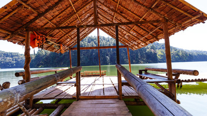 Small hut on bamboo raft in lake and camping site with pine tree