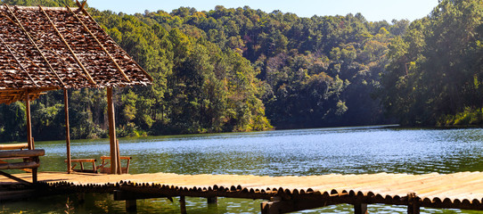 Bamboo bridge and hut in lake and camping site with pine trees