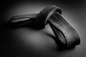 Black judo, aikido, or karate belt, tied in a knot, isolated on black background