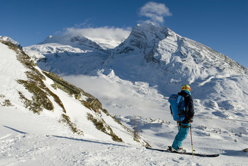 landscape of the Swiss Alps covered by snow and skier who practice ski mountaineering looking mountains and the horizon, on a sunny day, Switzerland, Simplon Pass, Mount Breithorn