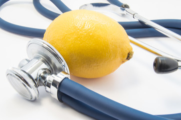 Yellow lemon lies near medical stethoscope which how would exam it. Concept to refer lemon and its juice as health food, it health benefits and use lemon in traditional medicine to treat colds
