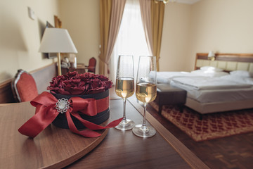 Elegant hotel room with rose decoration and champagne. Romantic weekend concept.