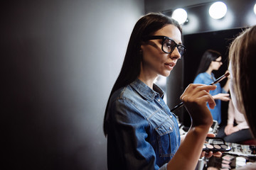 Pretty female makeup artist using the eye brush