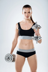 Athletic girl holding dumbbells on a grey background.