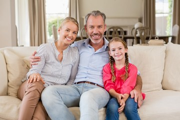 Portrait of smiling parents and daughter sitting