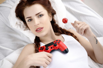 The concept of lifestyle and technology. Young girl playing on a console and have a piece of candy on the bed at home