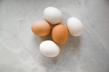 white and brown eggs on a white marble table