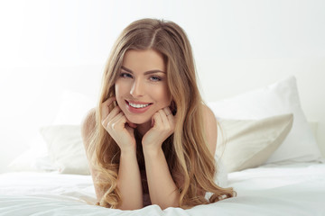 Young woman relaxing in the bed. Happy girl smiling