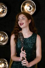 Beautiful girl with red long hair smiling. Bright make-up, red lips. Broad beautiful white smile. The green dress with sequins. The singer is standing near the microphone.