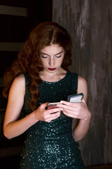 Young beautiful girl looking into the smartphone phone. haired slim girl in a green dress and long red hair. She looks at the phone down.