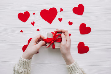 valentines day.female holding present  on white wooden background with  red hearts