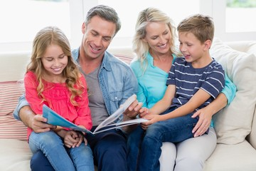 Parents and kids sitting together on sofa looking at photo album