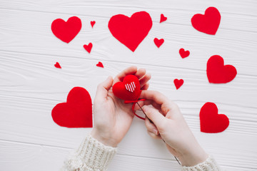 valentines day.female holding red hearts  on white wooden background