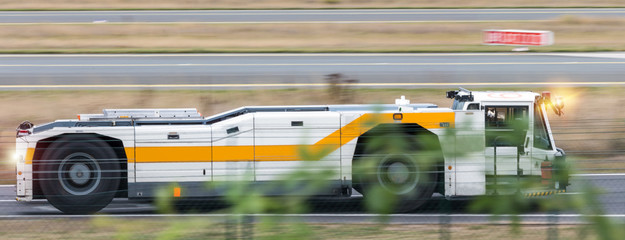 airport tractor speeding near the runway