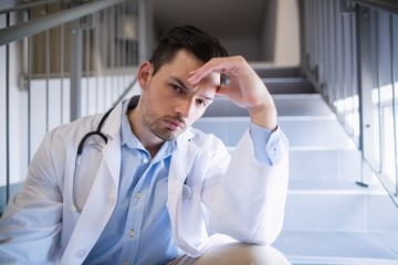 Portrait of thoughtful doctor sitting on staircase